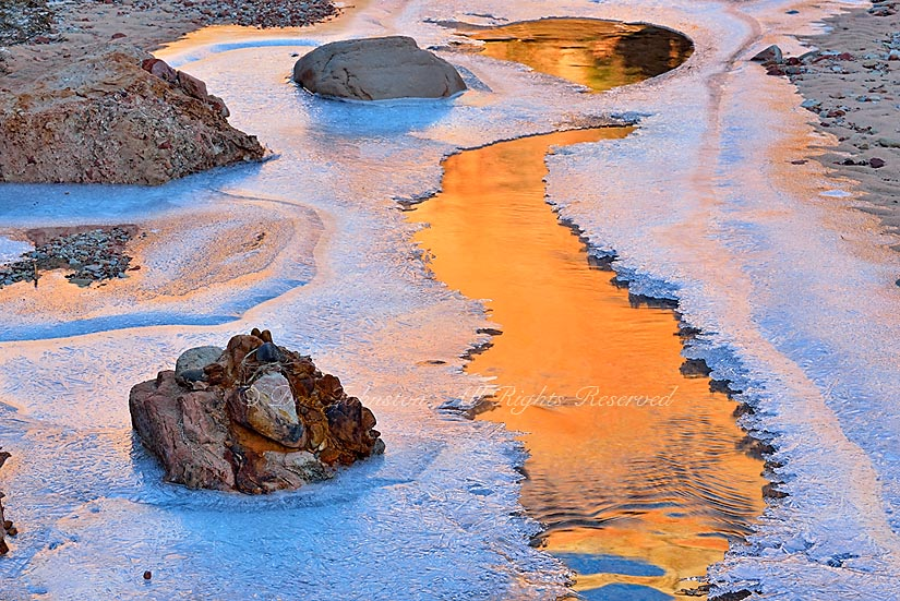 Ice formations along the Pine River with Zion Canyon wall reflections in open water, Zion National Park, Utah, USA